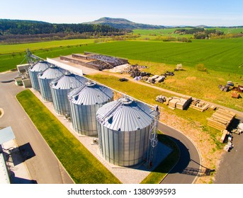 Aerial view of silos, storage tanks for rapeseed. Modern farm in agricultural landscape. Agriculture and environment in European Union.