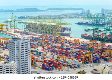Aerial view of Singapore harbor with commercial port full of freight containers, cargo ships and cranes on pier