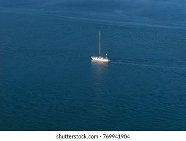 Aerial view of single yacht sailing in the blue open sea