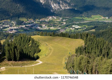 Aerial view of a ski slope with green meadows in summer (Monte Lussari). At the bottom of the valley the small village of Camporosso in Valcanale, Tarvisio, Friuli Venezia Giulia, Italy