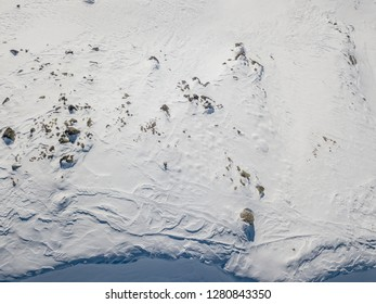 Aerial view of ski tracks in alpine region along cornice on ridge in mountains. Backcountry skiing