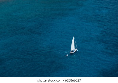 Aerial View from Sky of Antigua Island with Lonely Yacht in Distance