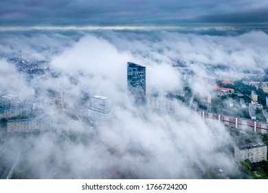 Aerial view of skyscraper Sky Tower in the fog in Wroclaw. Epic foggy morning in the city and tall building in the clouds. Wroclaw, Poland