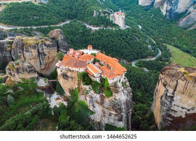 Aerial view of a slide from a drone on a panorama of a mountain range. Kalampaka city, Greece. View of the cliffs of Meteora and the monasteries of Meteora. Many ancient Orthodox monasteries summer