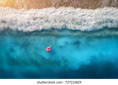 Aerial view of slim woman swimming on the pink swim ring in the transparent turquoise sea in Oludeniz,Turkey. Summer seascape with girl, beautiful waves, blue water in sunny day. Top view from drone