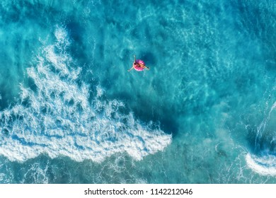 Aerial view of slim young woman swimming on the donut swim ring in the transparent blue sea with waves at sunset. Tropical aerial landscape with girl, clear water in Spain. Top view. Summer travel