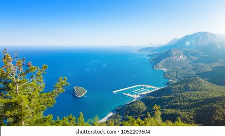 Aerial view of small Antalya Rat Island - popular diving spot in Mediterranean sea. Sunny summer day with blue sky, clear sea and green mountains near Antalya, Turkey.