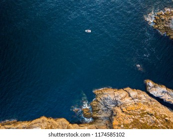 Aerial view of a small boat in the Galician coast, at the opening of the Ria de Pontevedra, were the Atlantic ocean meets the land.