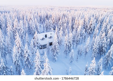 An aerial view of a small cottage in a snowy, frosty wintery Finnish taiga forest, Lapland, Northern Europe.