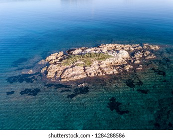 Aerial view of a small island surrounded by turquoise water, North Sardinia, Cala Sassari