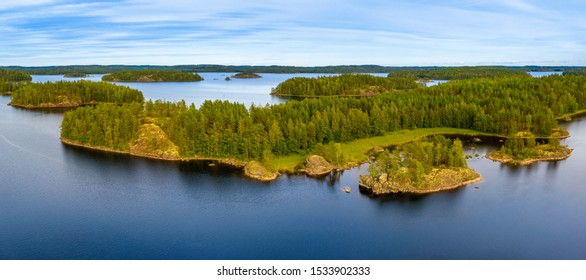 Aerial view of of small islands on a blue lake Saimaa. Landscape with drone. Blue lakes, islands and green forests from above on a cloudy summer morning. Lake landscape in Finland