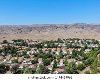 Aerial view of small neighborhood with dry desert mountain on the background in Moorpark, Ventura County in Southern California. USA
