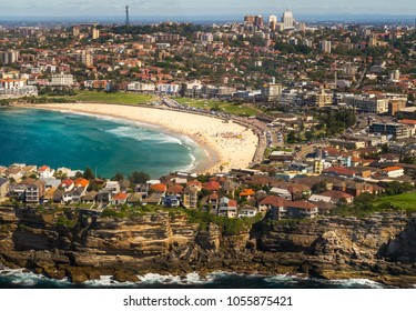 Aerial view from a small plane of Bondi beach, Sydney, Australia. A group of people can be seen gathered on the golden sand.