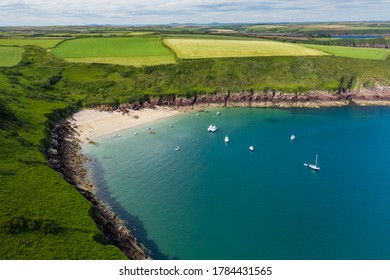 Aerial view of a small, sandy beach in a rocky bay (Watwick Bay, Milford Haven, Wales)