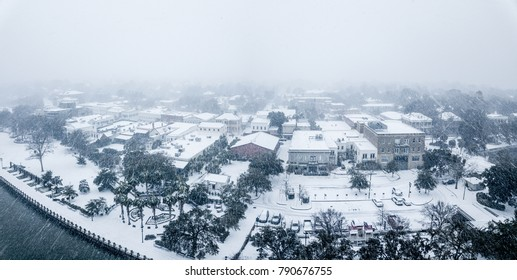 Aerial view of small seaside town during blizzard and heavy snow