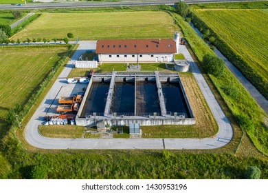 Aerial view of small sewage treatment plant with wastewater tanks and filters, fields with crops surrounding the plant, Slovenska Bistrica, Slovenia