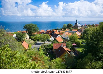Aerial view of small town - with beautiful, small houses and a church - at the seaside, Gudhjem, Bornholm, Denmark