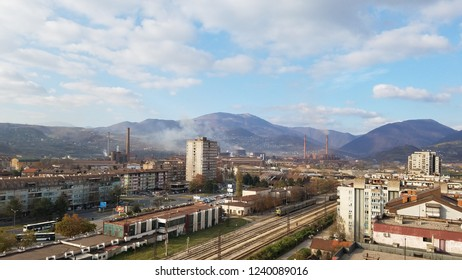 Aerial view of a small town with a factory. Landscape view of Zenica, Bosnia and Herzegovina in clear, sunny weather with clouds in the sky. Railway, buildings, bus station and steel factory.