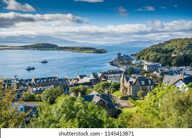 Aerial view of small town Oban in Scotland. Scattered trees, small village and sea in the background, bright sunny day.
