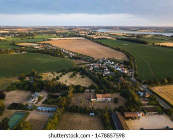 Aerial view of a small traditional village in the Suffolk countryside. The village is surrounded by farm fields growing different crops