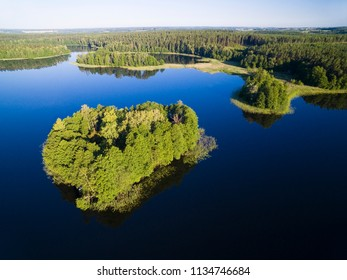 Aerial view of small uninhabited island (Wyspa Pozeracza Serc) on lake with sky reflected in calm water, Krzywa Kuta Lake, Mazury, Poland