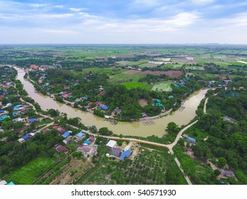 Aerial view of a small village and paddy field near the river in Thailand.