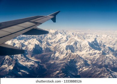 Aerial view of the snow capped Himalayas mountain in Nepal from a plane on a sunny winter day