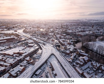 Aerial view of snow compromised rail and road networks. Snow, ice and winter weather conditions close railway links and shut roads causing transport delays and dangerous conditions.