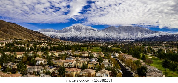 Aerial view of snow covered San Gorgonio and Little San Bernardino Mountains above Yucaipa, California on a winter day with blue sky, white and grey clouds, white snow, houses, Crafton Hills