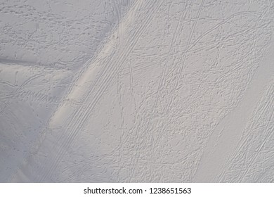 Aerial view of snow fields with abstract footprints