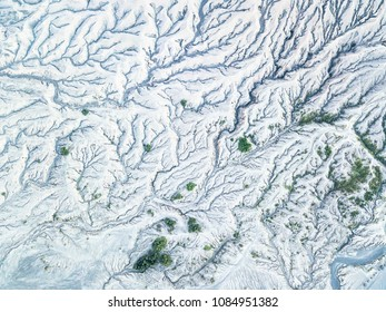 Aerial view of snow mountain terrain and erosion the surface around the volcano at winter. Beautiful bird eyes view of nature and landscape. Top view from drone. Texture of the earth.