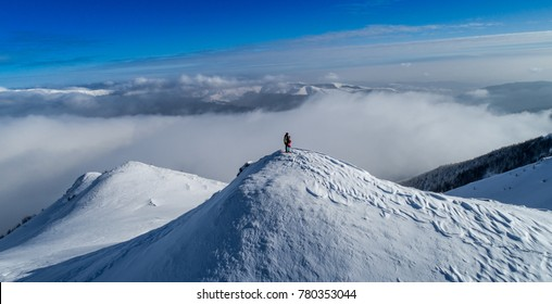 Aerial view of a snowboarder on top of the mountain. Snowboarder on the summit. Mountain landscape. Snowboard. Freeride. Drone photo. Aerial landscape. Winter aerial photography. Snow on the mountain