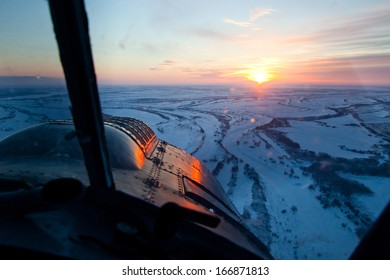 It is aerial view of the snow-covered plain at the winter sunset from the cockpit of old airplane.