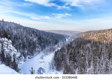 Aerial view of snow-covered trees in the mountains. Valley of the frozen river