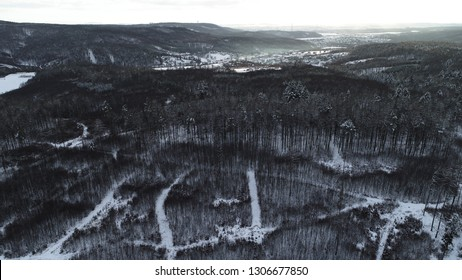 Aerial view of a snowy dark forest during sunset.