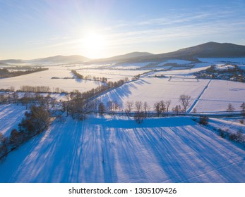 Aerial view of snowy landscape with river in the evening. Valley in national park Sumava, Czech republic, European union.