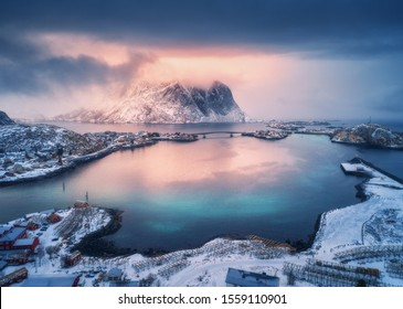 Aerial view of snowy mountain, village on sea coast, orange sky at sunset in winter. Top view of Reine, Lofoten islands, Norway. Moody landscape with high rocks, houses, rorbu, reflection in water