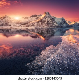 Aerial view of snowy mountains, blue sea with frosty coast, reflection in water and purple sky at colorful sunset in Lofoten islands, Norway. Winter landscape with snow covered rocks, fjord with ice