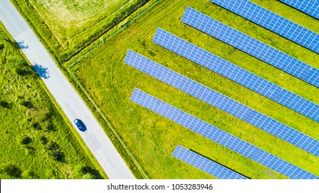 Aerial view of solar panels and car on the road. Renewable solar energy theme for background. Solar power station from drone view.