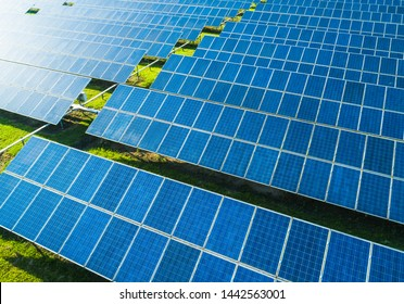 Aerial view of Solar Panels Farm (solar cell) with sunlight. Drone flight over solar panels field, renewable green alternative energy concept.