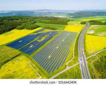 Aerial view of solar power plant. Solar farm system from above. Large photovoltaic power station next to the highway. Source of ecological renewable energy.