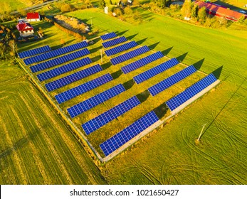 Aerial view of solar power plant. Photovoltaic power station supplying electricity to small town in countryside. Renewable solar energy in the city.