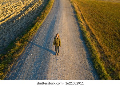 Aerial view of solitary woman on a footpath in the country side