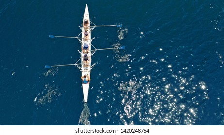 Aerial view of sport canoe operated by team of young atheletes in emerald open ocean sea