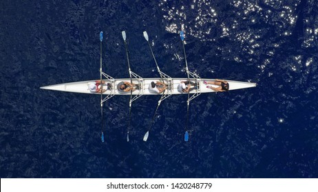 Aerial view of sport canoe operated by team of young atheletes in deep blue open ocean sea