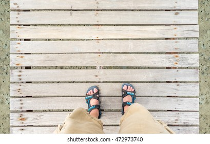 aerial view of sport shoe with short pants stand on grunge wood bridge at sea Leave space on top for adding your text.