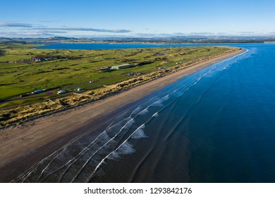 Aerial view of St Andrews' famous West Sands beach with waves rolling in. This peninsula also contains the famous golf links courses.