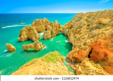 Aerial view of staircase leading to the base of cliffs of Ponta da Piedade in Lagos Bay with turquoise sea. Sandstone formations in Lagos, Algarve, Portugal. Boat trip between cliffs, summer holidays