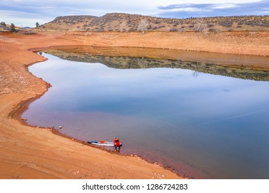 Aerial view of a stand up paddler on lake shore , typical winter scenery in northern Colorado foothills with no snow and low water level