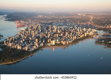 Aerial view of Stanley Park and Downtown Vancouver, BC, Canada. During a hazy sunny sunset.